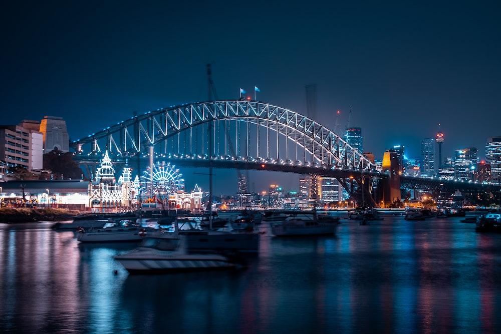 gray concrete bridge over river near buildings with lights