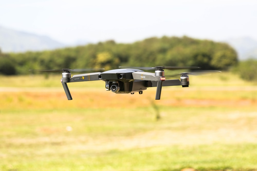 selective focus photography of flying gray and black quadcopter drone during daytime