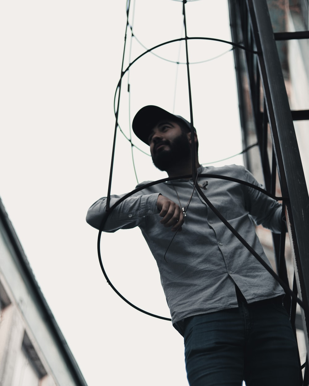 low angle photography of man wearing gray button-up long-sleeved shirt and cap standing on black metal frame