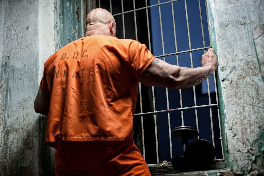 Man in prison looking out from bars
