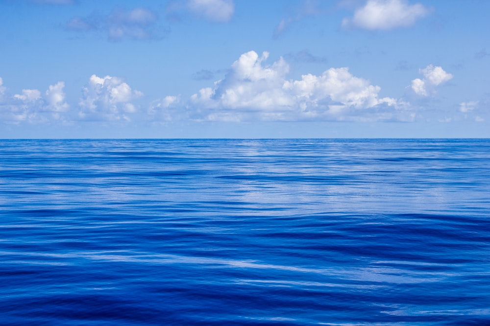 blue body of water under white and blue sky