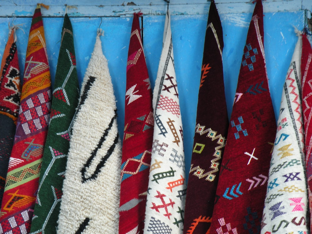 assorted-colored tribal towels hanging on blue wall