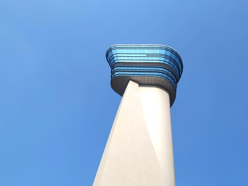 low-angle photography of white and blue tower building