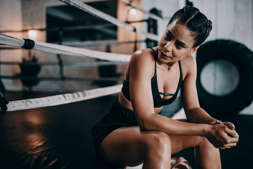woman wearing black sports bra and black shorts sitting near boxing arena