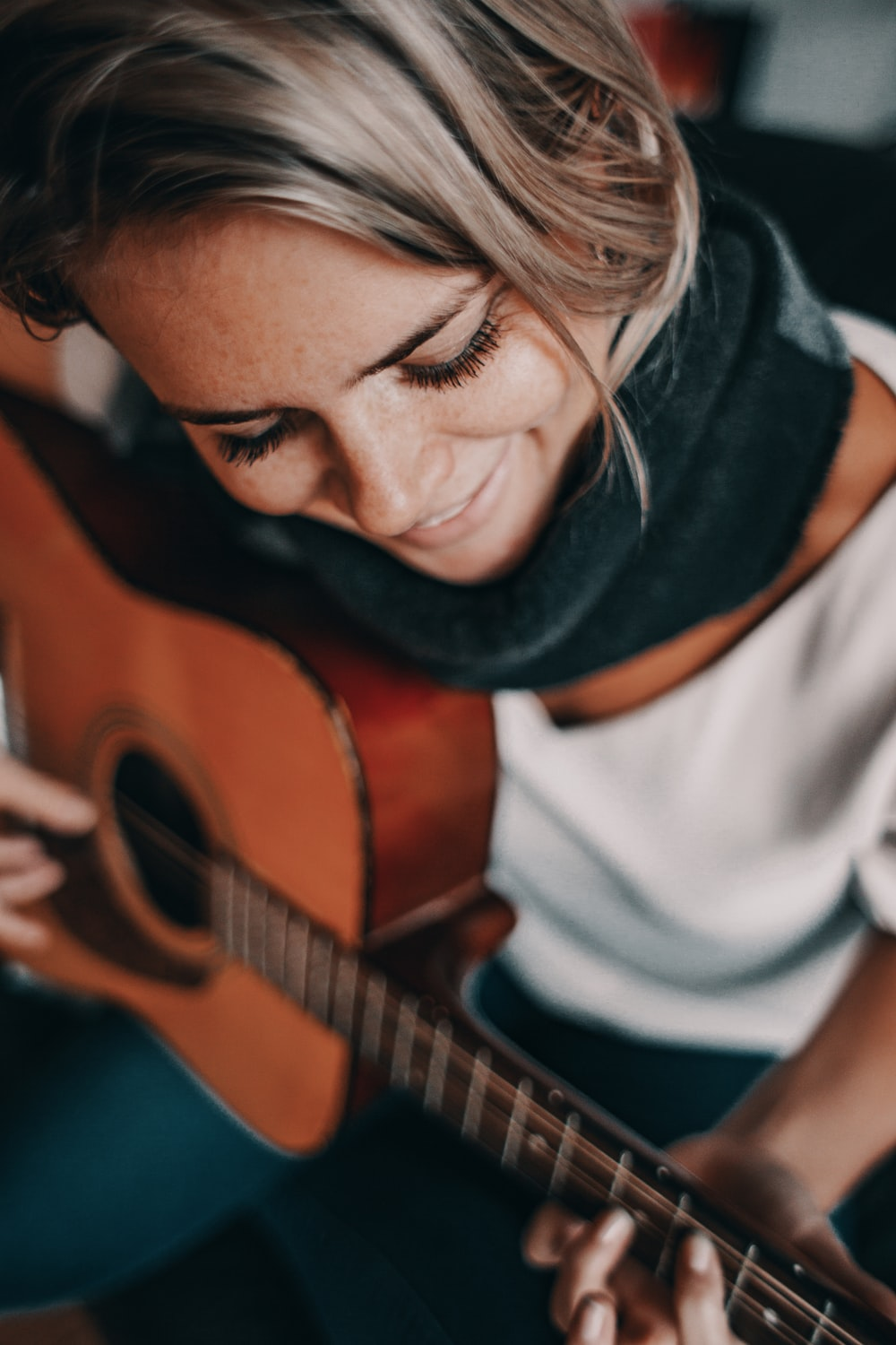 woman in white top playing acoustic guitar