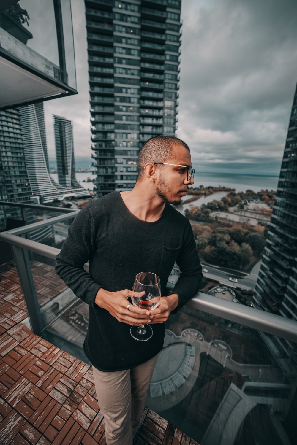 man standing and holding near empty wineglass leaning beside gray framed clear glass building balcony railing at the city during day