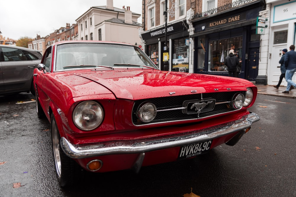 red first generation Ford Mustang coupe parking near road