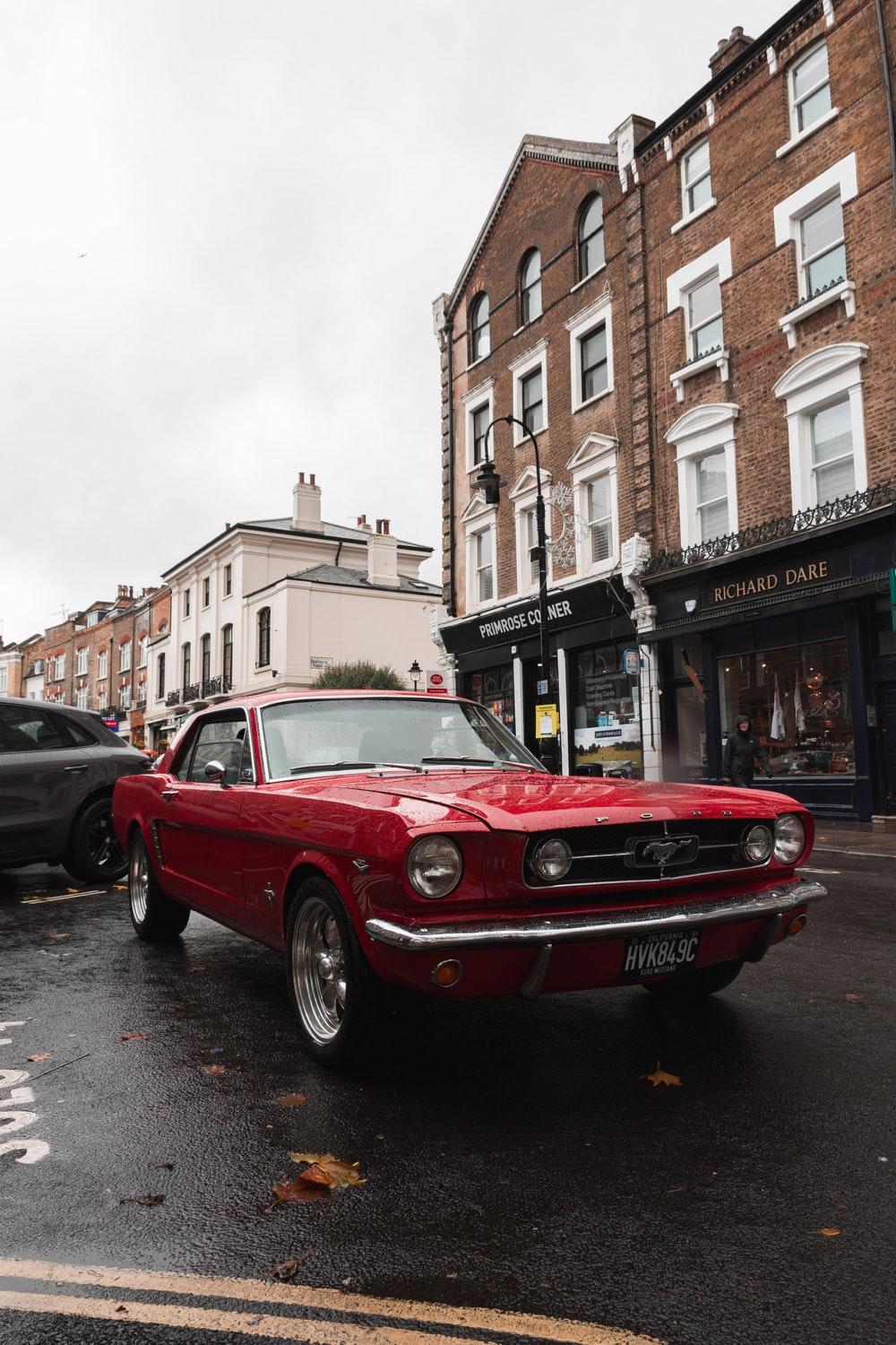 classic parked red Ford Mustang coupe near buildings and cars during day