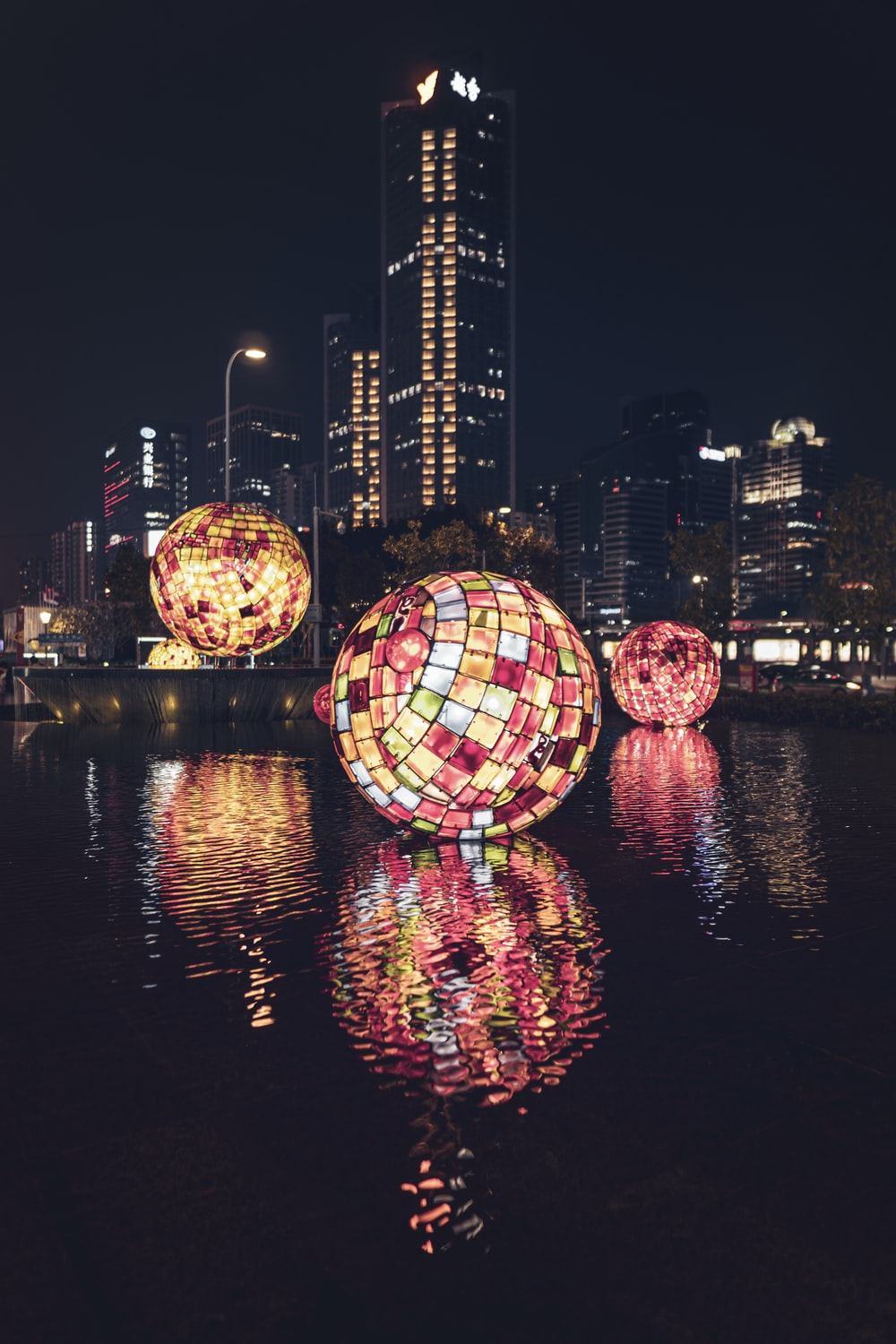 decorative balls with lights floating on body of water at the city during nighttime