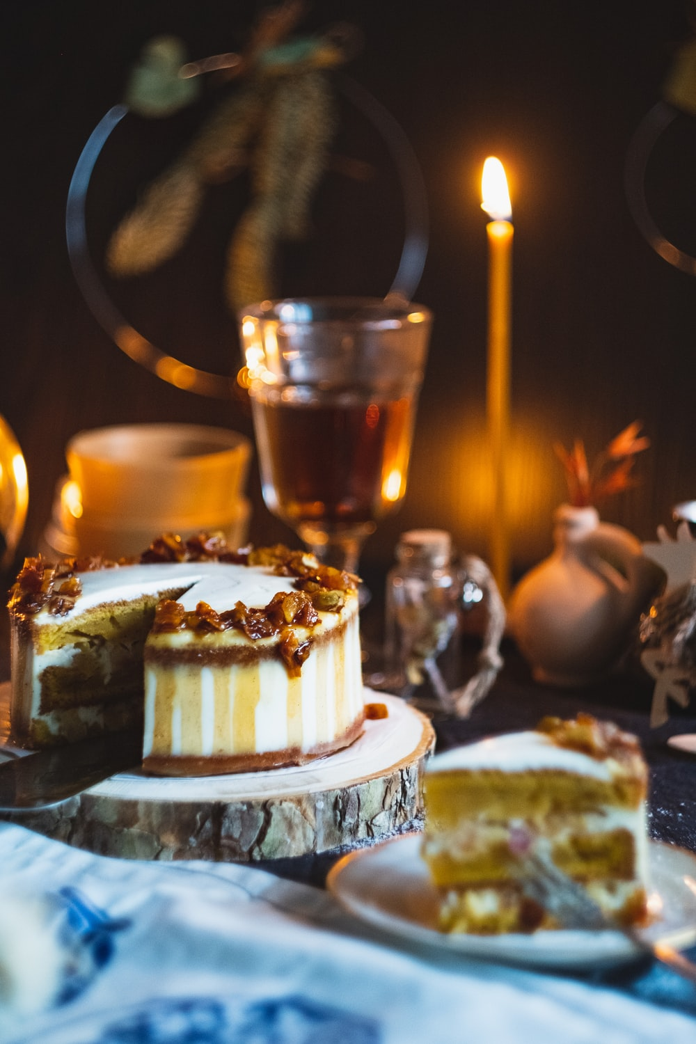 macro photography of sliced cake near glass cup and candle