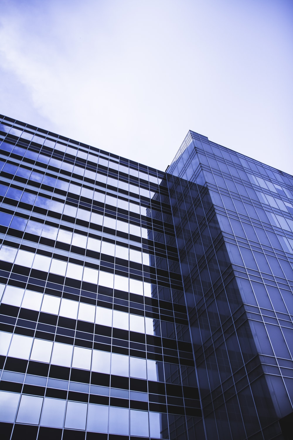 architectural photography of blue glass walled high-rise building under white and blue sky