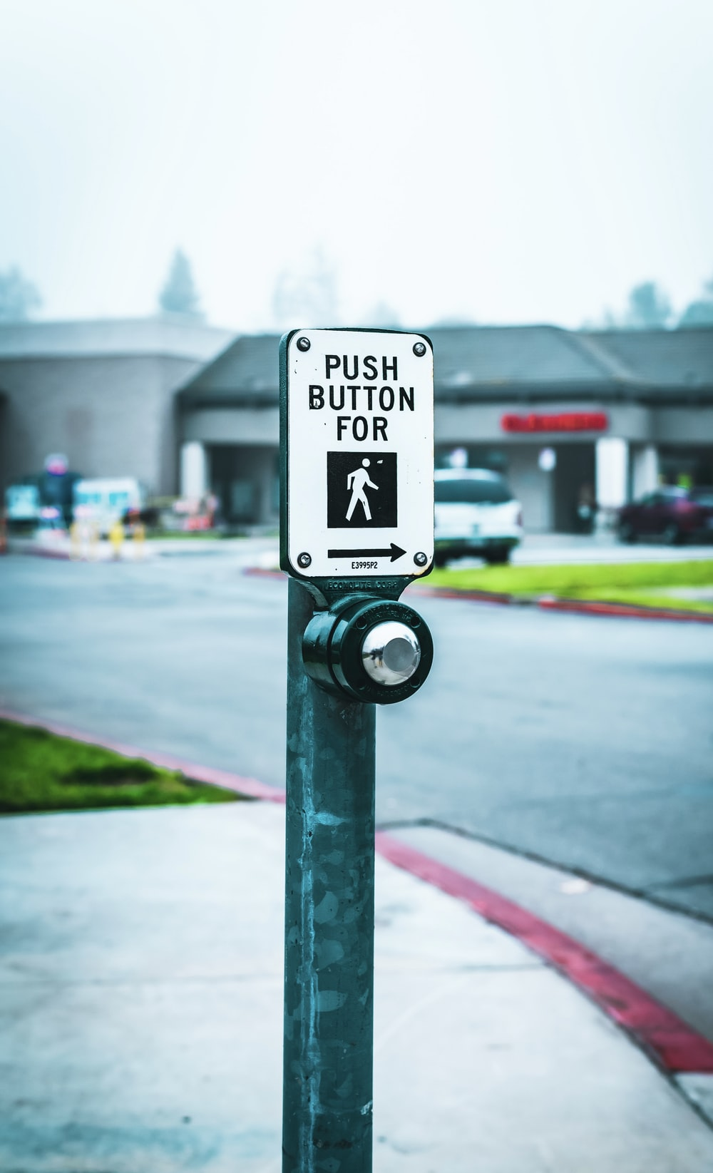 push button for walk post beside the road during daytime