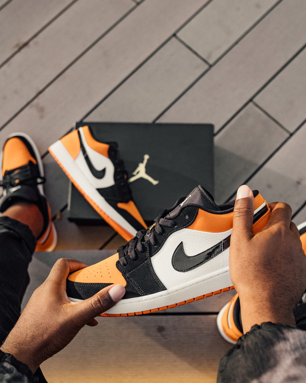 person sitting and holding white, orange, and black Air Jordan 1 low-top sneaker