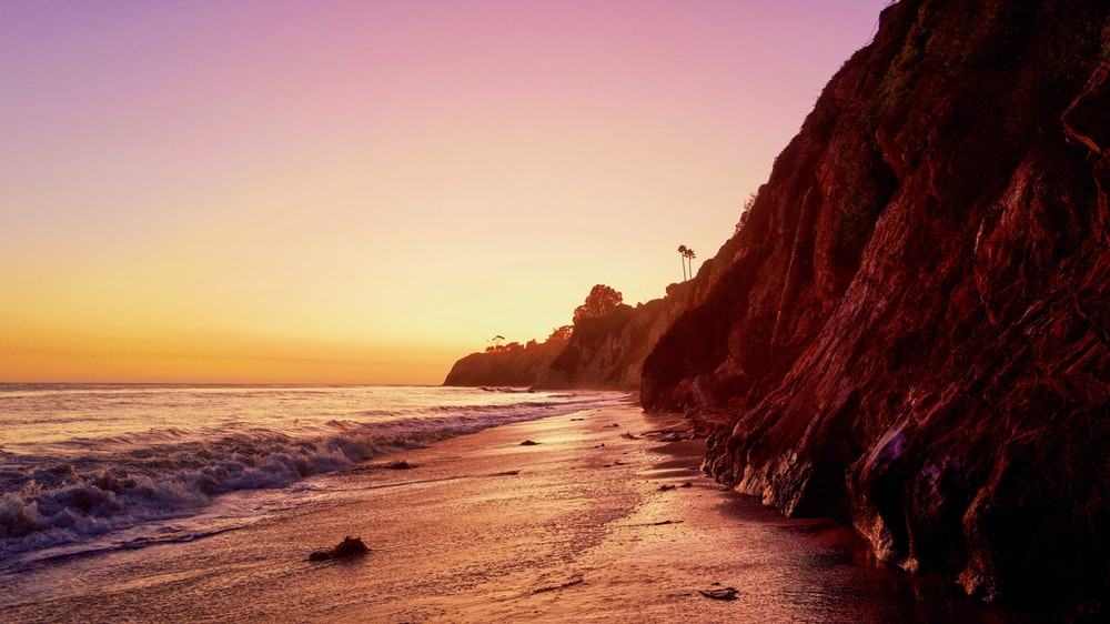 landscape photography of cliff viewing body of water under orange sky
