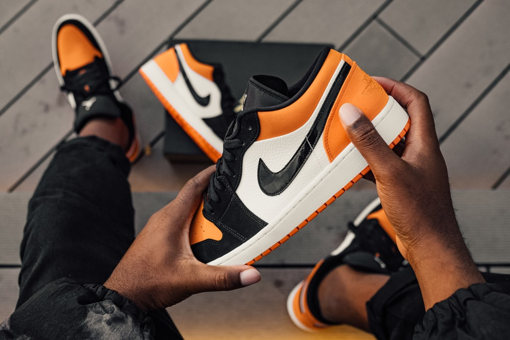 person sitting and holding orange-white-and-black Nike SB low-top sneaker