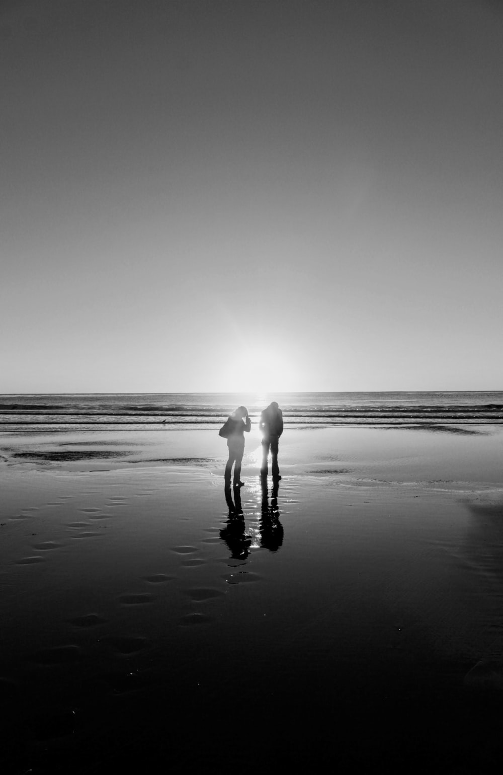 two people standing on seashore during day