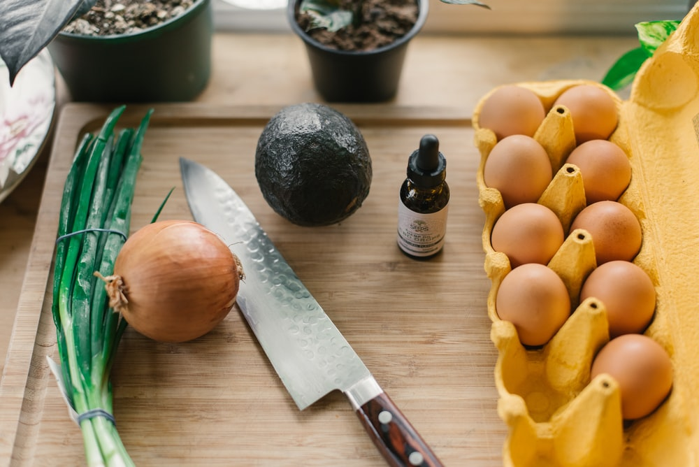 tray of eggs beside drop bottle, vegetables, and knife