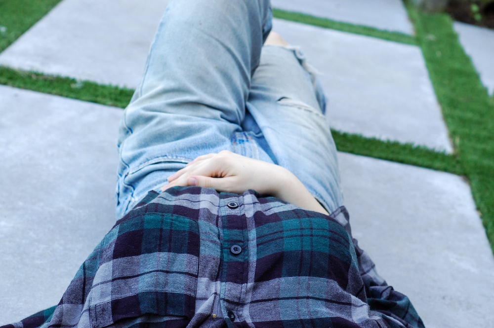 person wearing distressed blue denim bottoms and blue, purple, and black plaid button-up shirt lying on concrete pavement