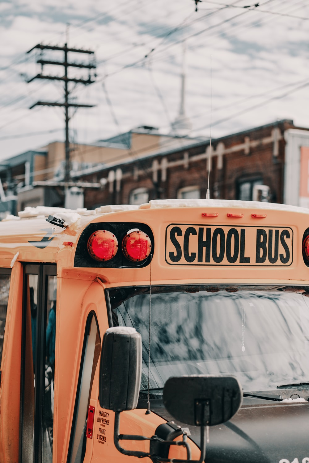 yellow school bus near building under white and blue sky