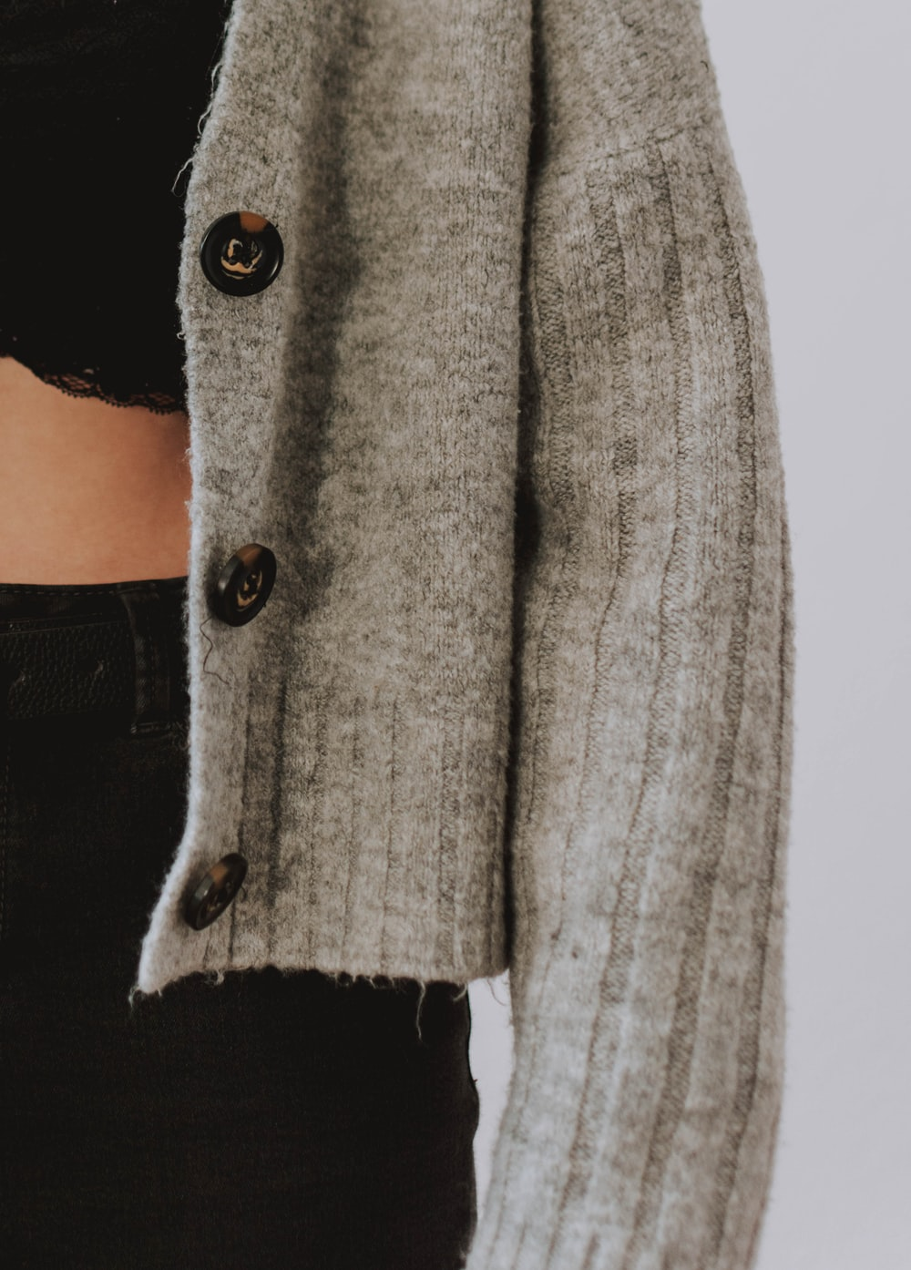 person wearing gray knit button-up sweater
