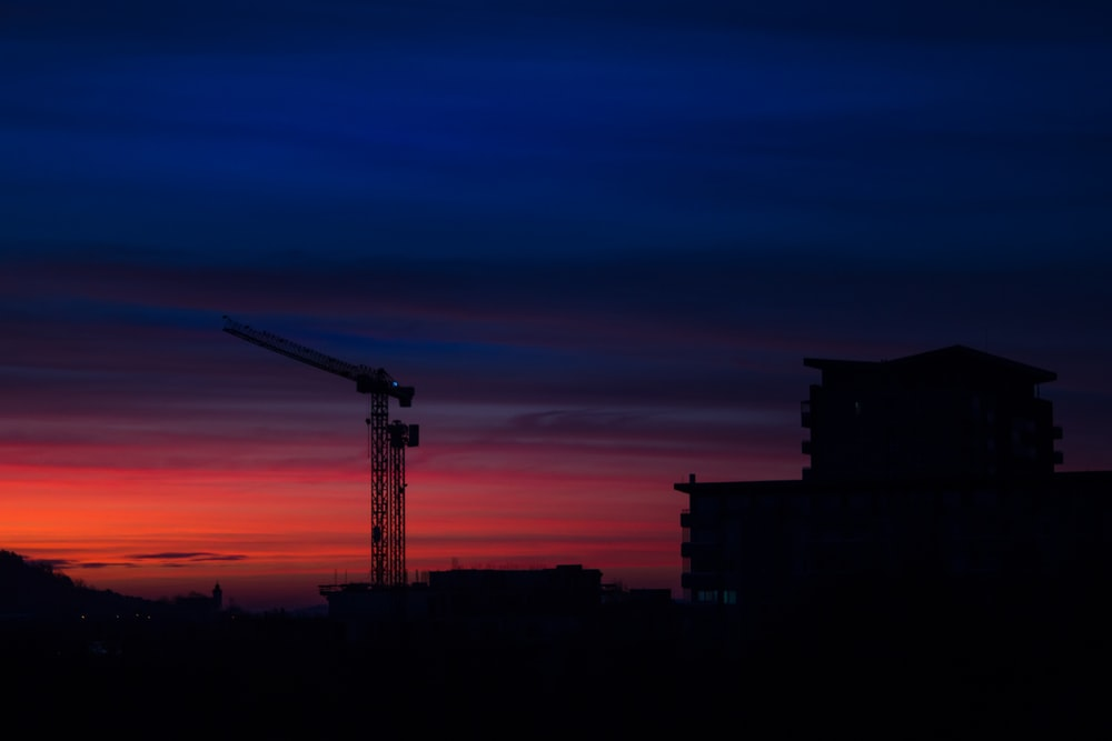 silhouette of tower crane during golden hour