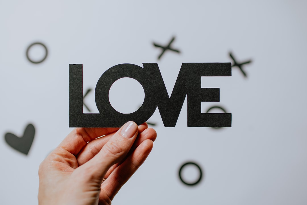 Hand Holding A Paper Cutout of the Word Love - unsplash