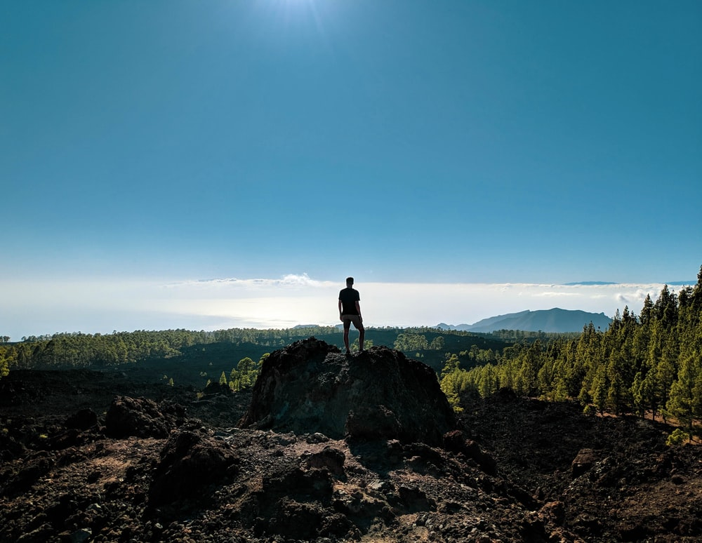 man standing on rock viewing mountain under blue and white sky