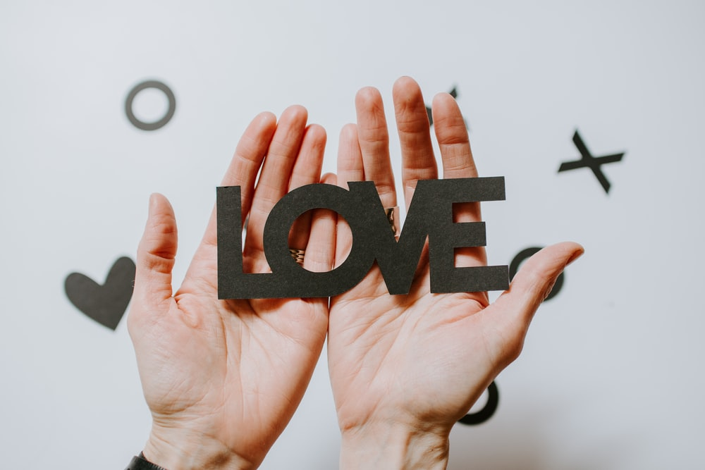 person holding love word cutout paper