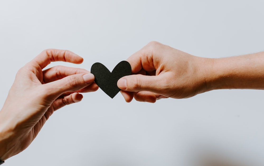two person holding papercut heart