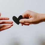 person reaching black heart cutout paper