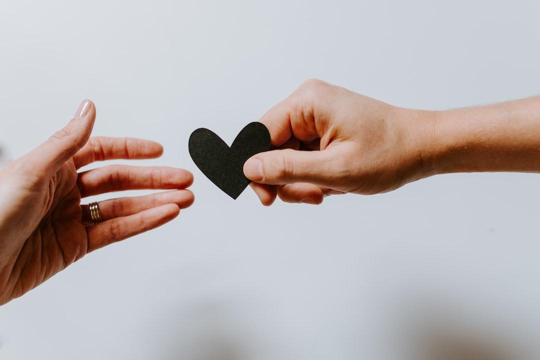 Man handing a woman a heart shape
