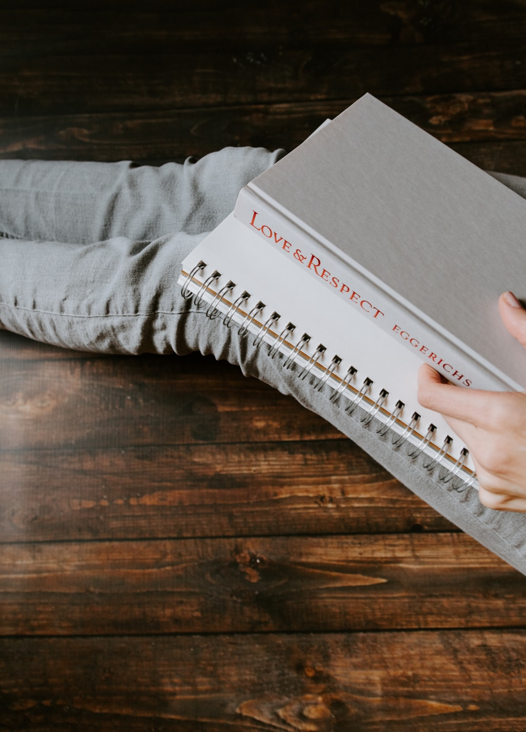 """Woman's lap holding book titled """"Love & Respect"""" and a notebook"""