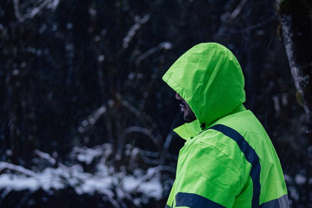 man wearing green and blue hooded jacket