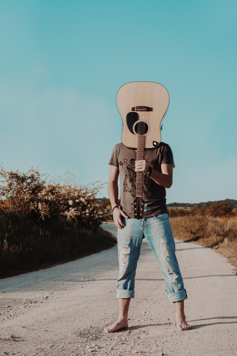 man holding brown acoustic guitar