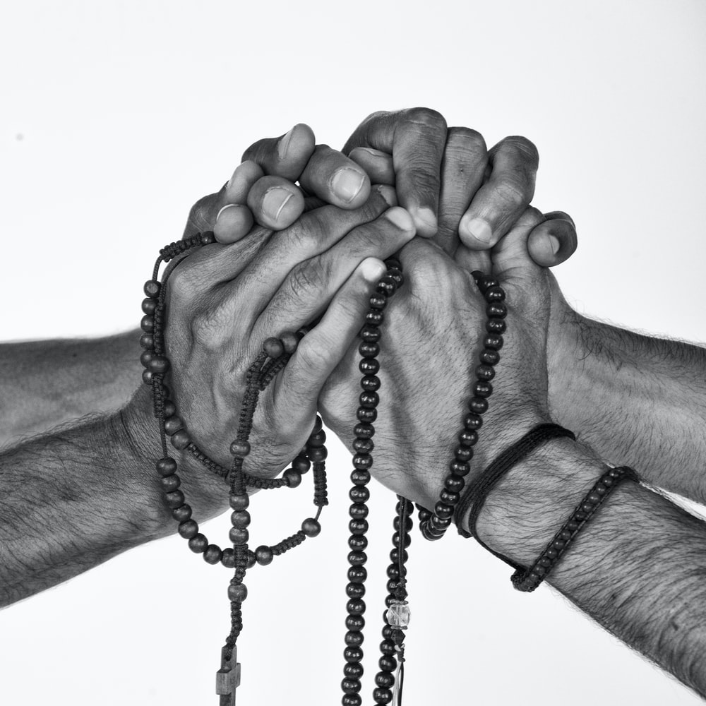 greyscale photograph of person holding prayer beads