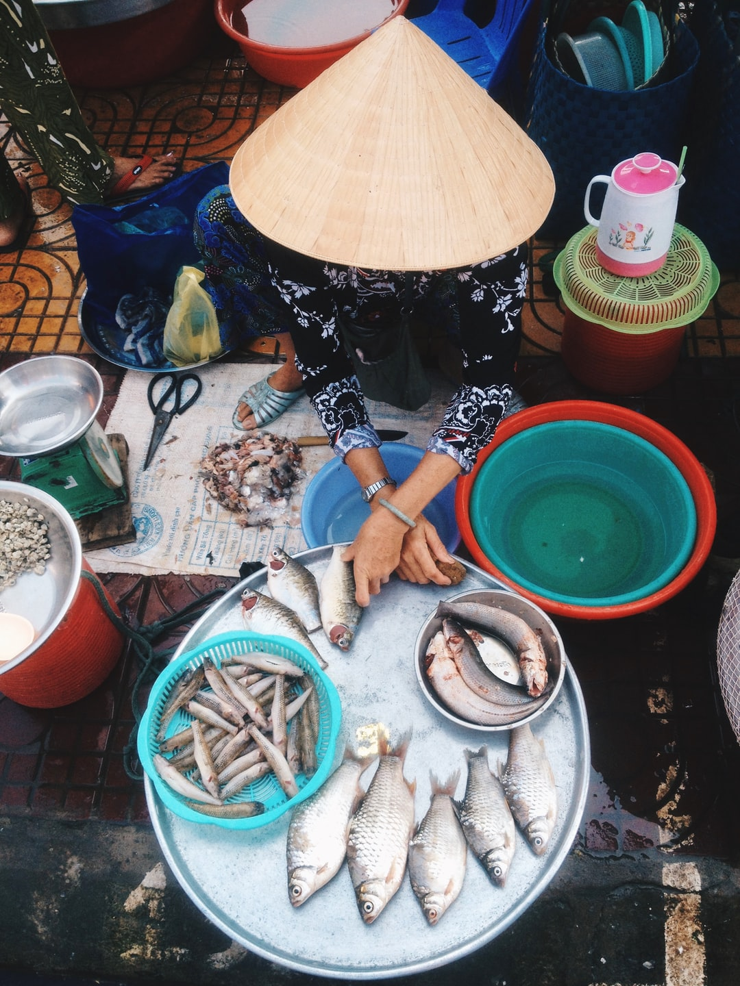 A woman cuts the tails off of fish in a market in VietNam