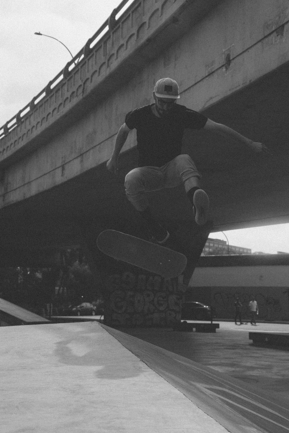 greyscale photograph of man doing tricks while riding skateboard