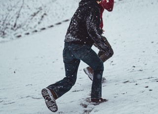 man wearing black hooded jacket walking on the snowy field
