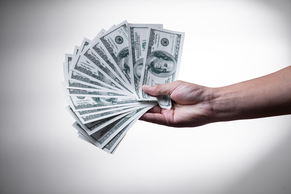 person holding 100 US Dollar banknote