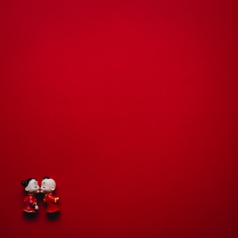 girl and boy wearing red dress figurines