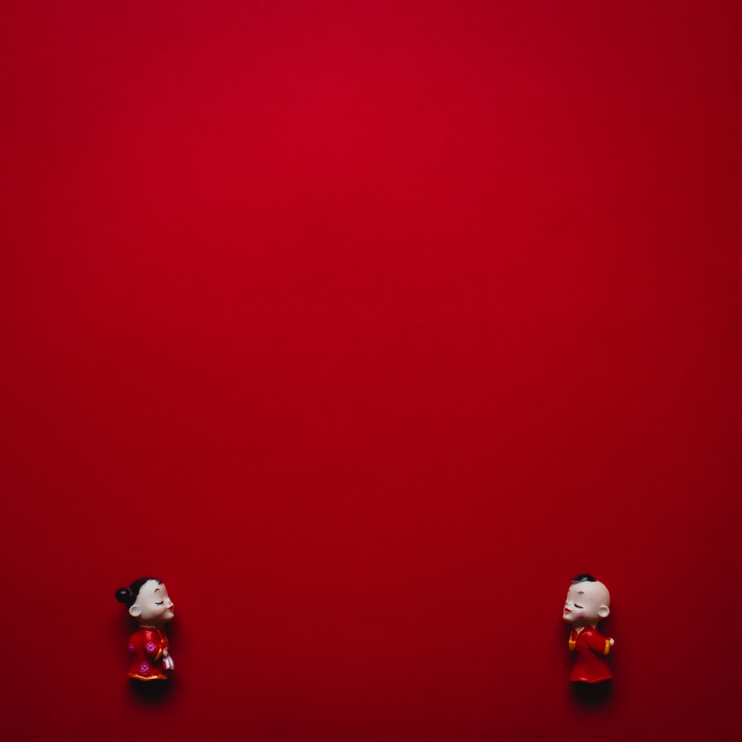Two figurines, people, longing to embrace in a kiss, facing each other from opposite sides of lower portion of an all red background.