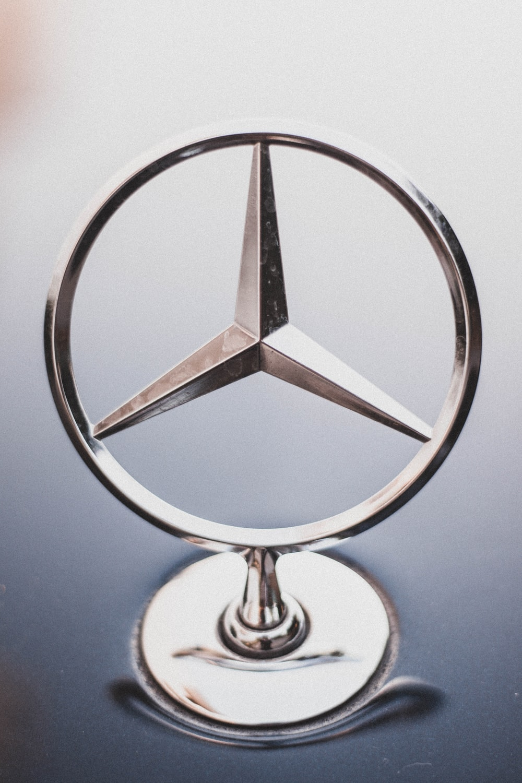 selective focus photography of Mercedes-Benz hood emblem