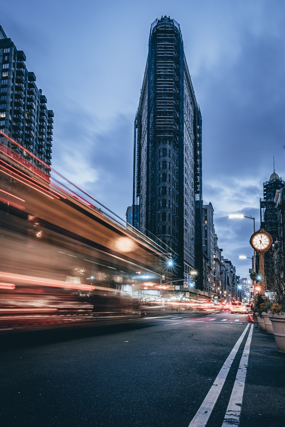 time-lapse photography of vehicles passing on road near Flat Iron building, New York