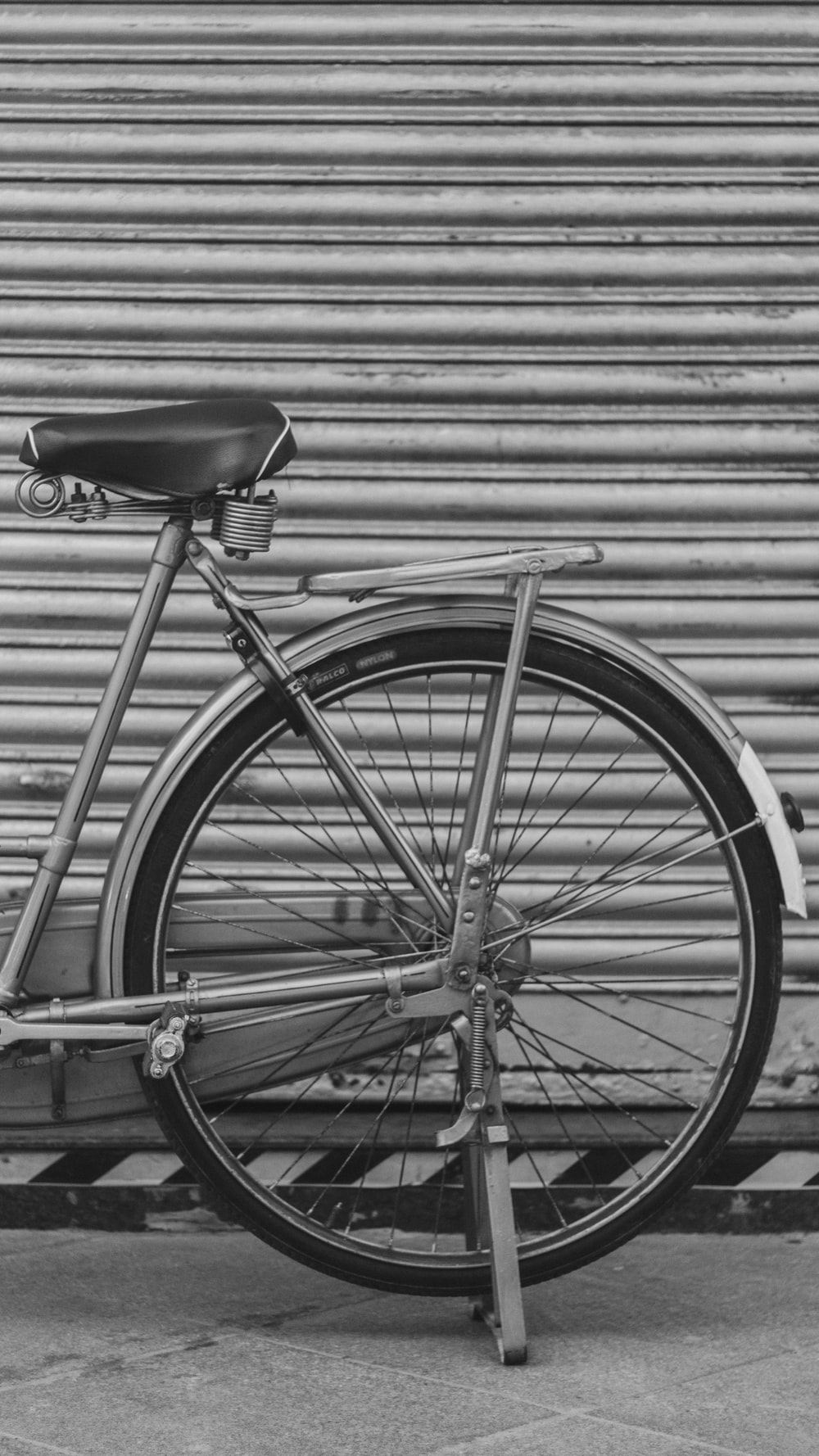 grayscale photo of bicycle parked in front of building with roller shutter