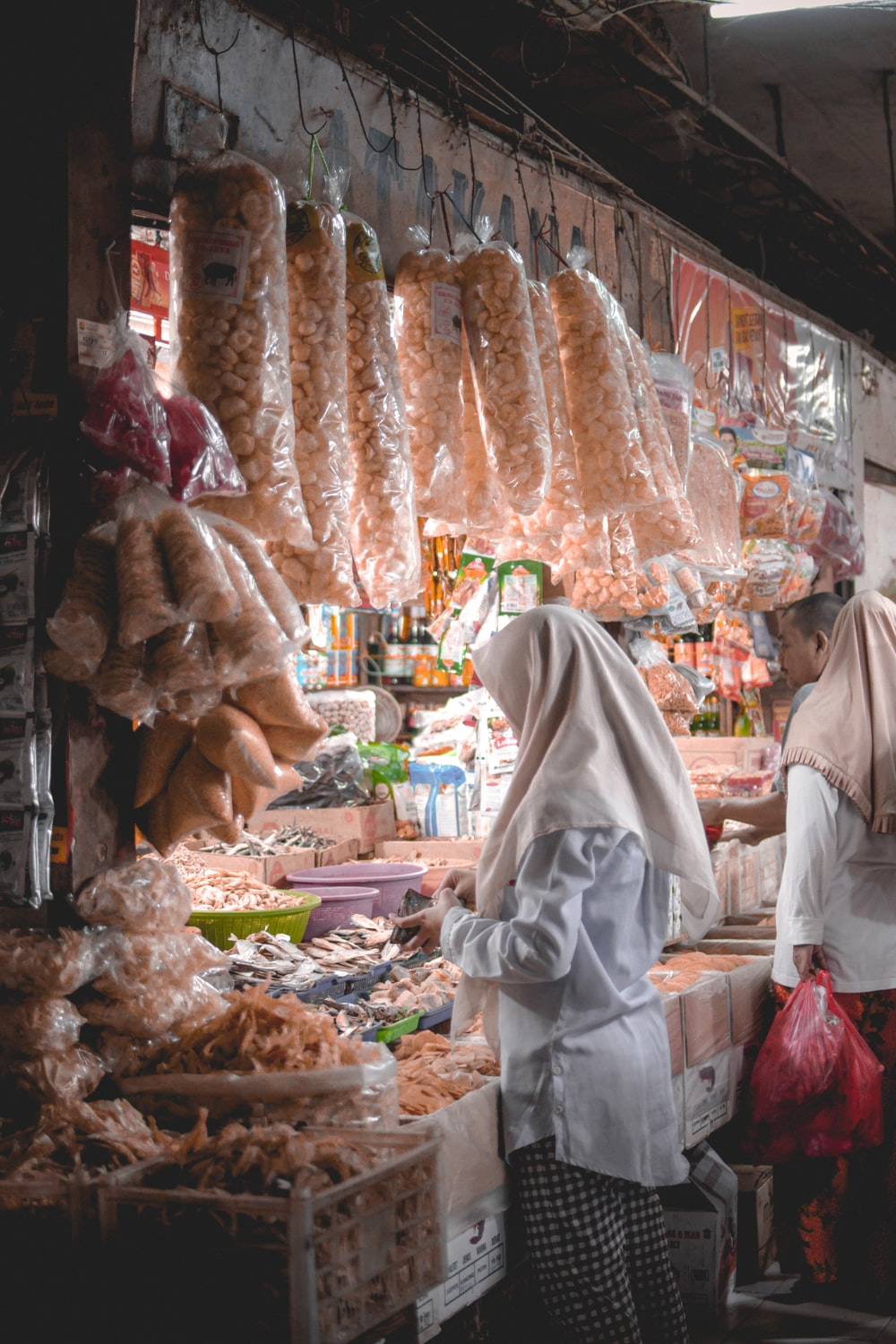 two women wearing hijab standing in front of store