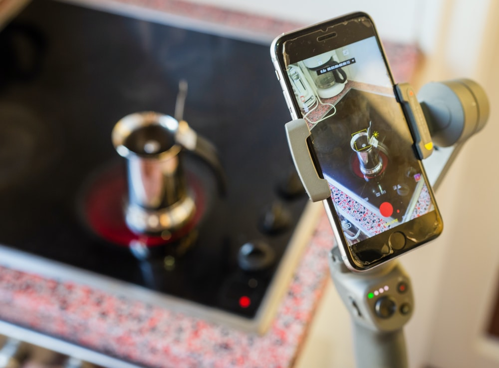 black smartphone on holder taking video of cup