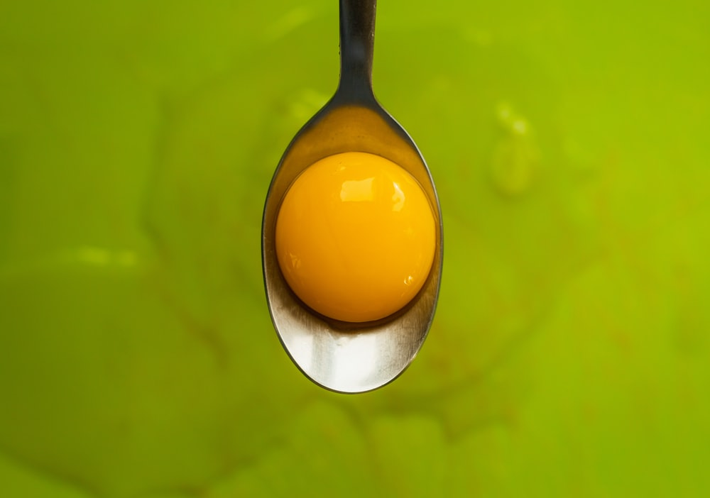 selective focus photography of eggyolk on gray spoon