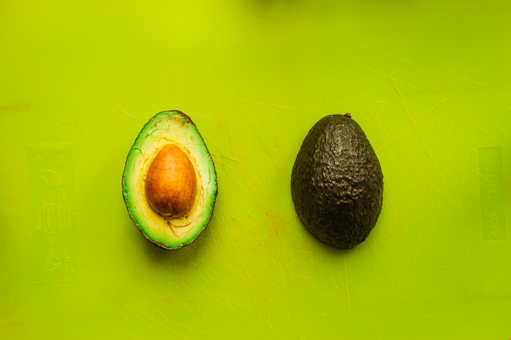 sliced avocado on green surface