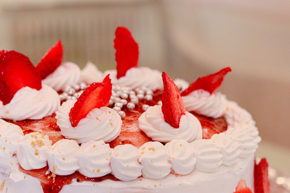 selective focus photography of white and red icing-covered cake
