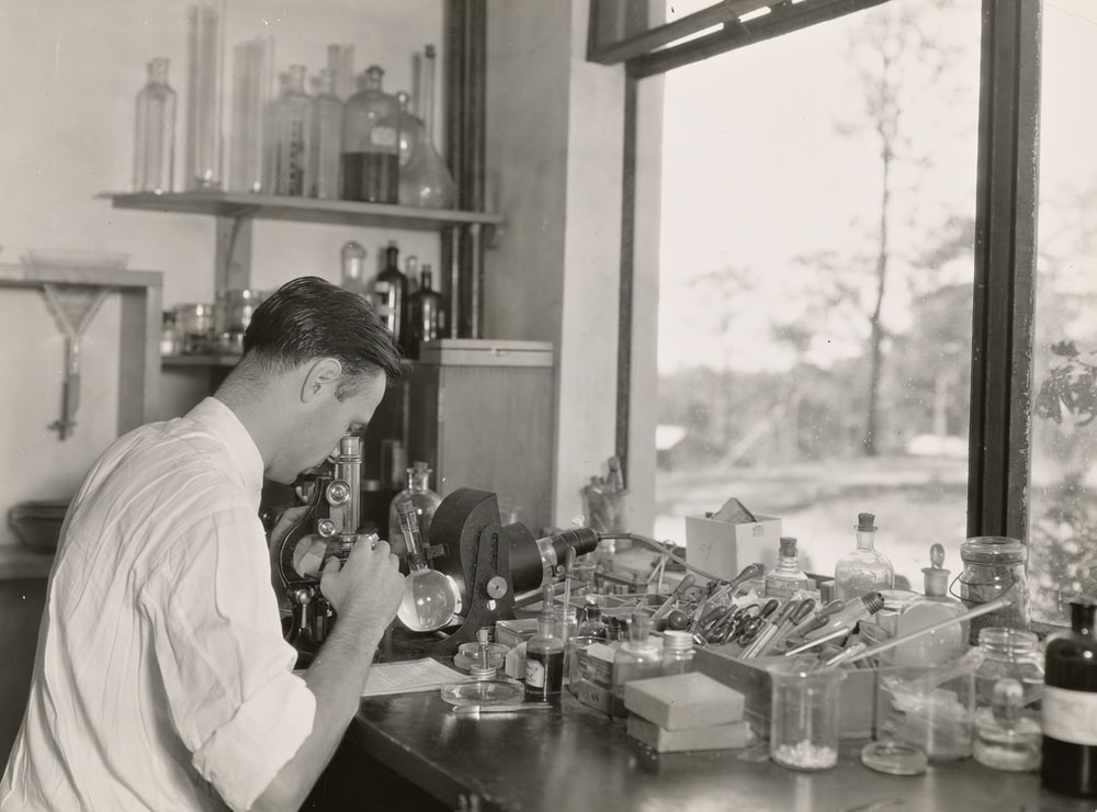 grayscale photography of scientist using microscope in the zoological division